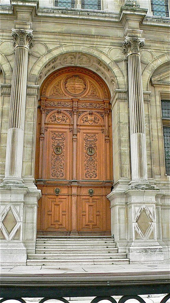These doors are some beautiful wooden doors in the center of the façade of the Hôtel de Ville, Paris.  This is the 'city hall' of the City of Paris.  They look far different from any I've seen on a city hall in the US!