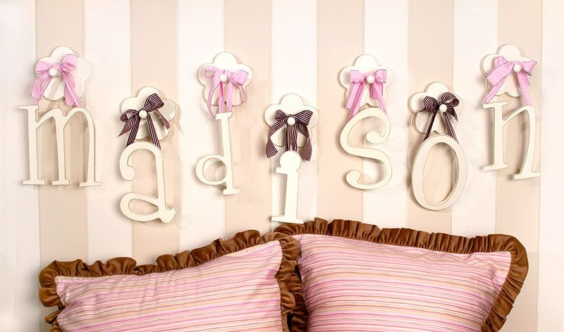 hanging wooden wall letters with pink ribbon and striped wall paint http