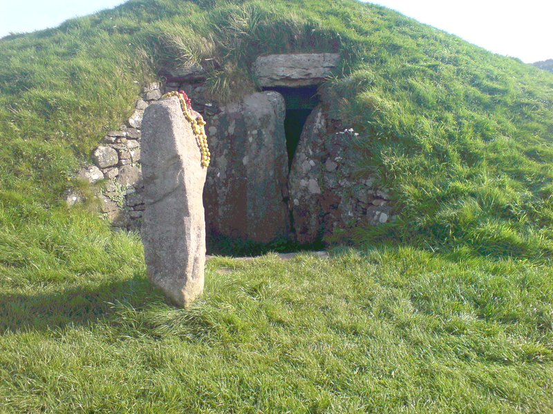Bryn Celli Ddu in North Wales, from the southwest side, at the back of the chamber;  a carved stone with a twisting, serpentine design stood in the burial chamber – it has since been moved to the National Museum of Wales and replaced with a replica standing outside;  photo by ljanderson977