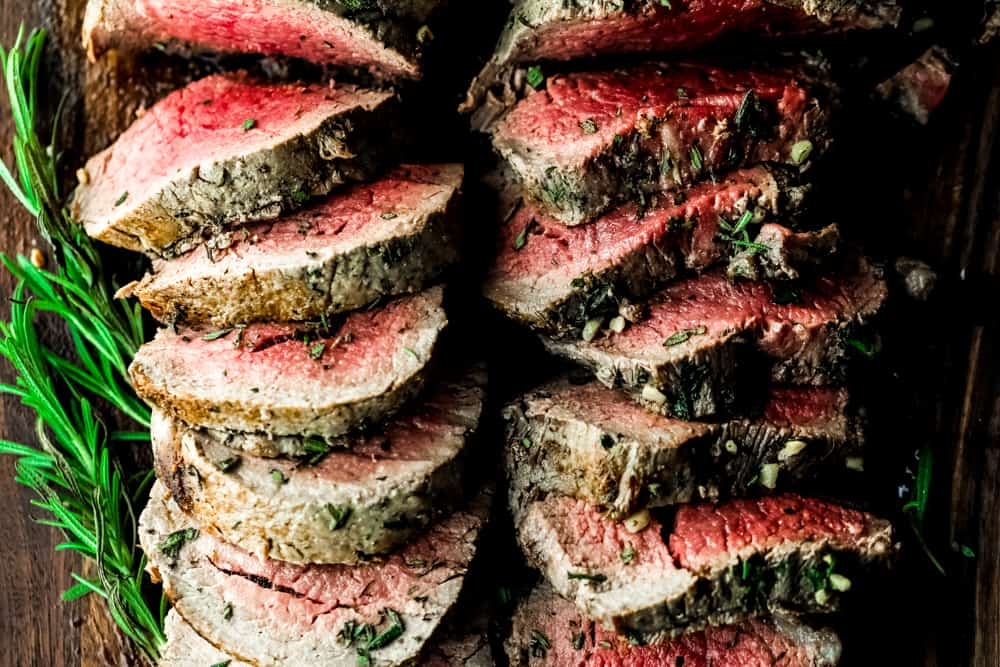 Garlic Herb Butter Beef Tenderloin is a juicy tenderloin seared and roasted with herb butter seasonings all baked to a buttery perfection! Impress your guests with this beautiful beef tenderloin! #beeftenderloin