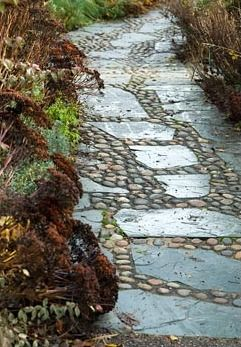 Path of slate and sea washed pebbles in the West Country town garden, one of the model gardens. RHS Garden Rosemoor, Great Torrington, Devon, UK