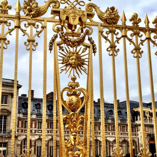 Gates At Palace Of Versailles With Sun King Symbol Of Louis Xiv