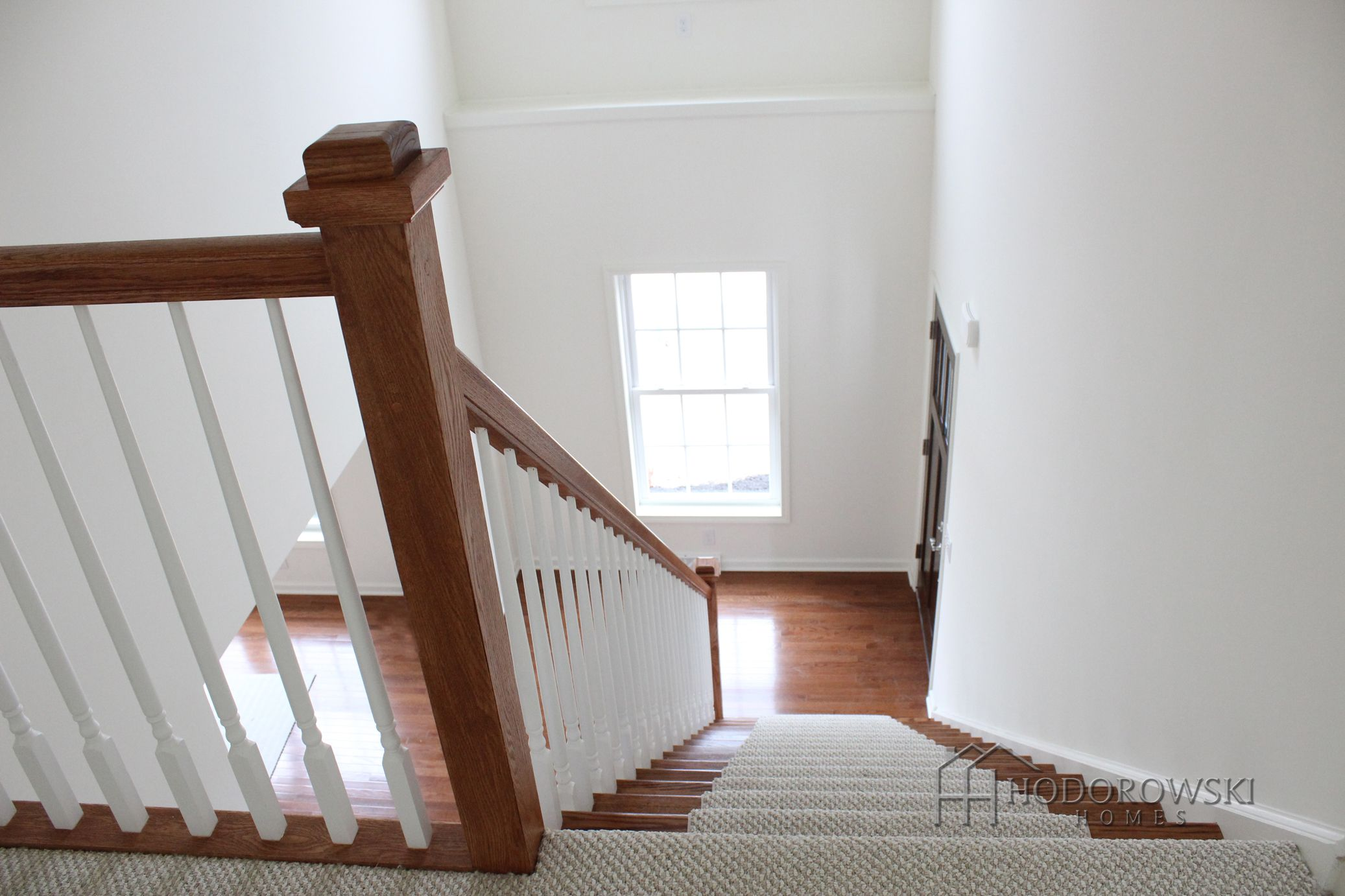White spindles and a light carpet runner to soften the look of dark hardwood.