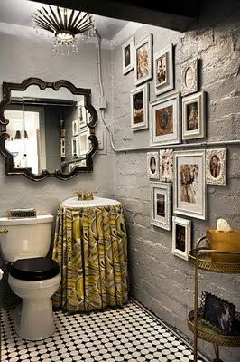 Love the non-traditional shape of the mirror and the skirt covering the small sink.  The grey on grey decor with black accents makes this small bathroom comfortable looking.