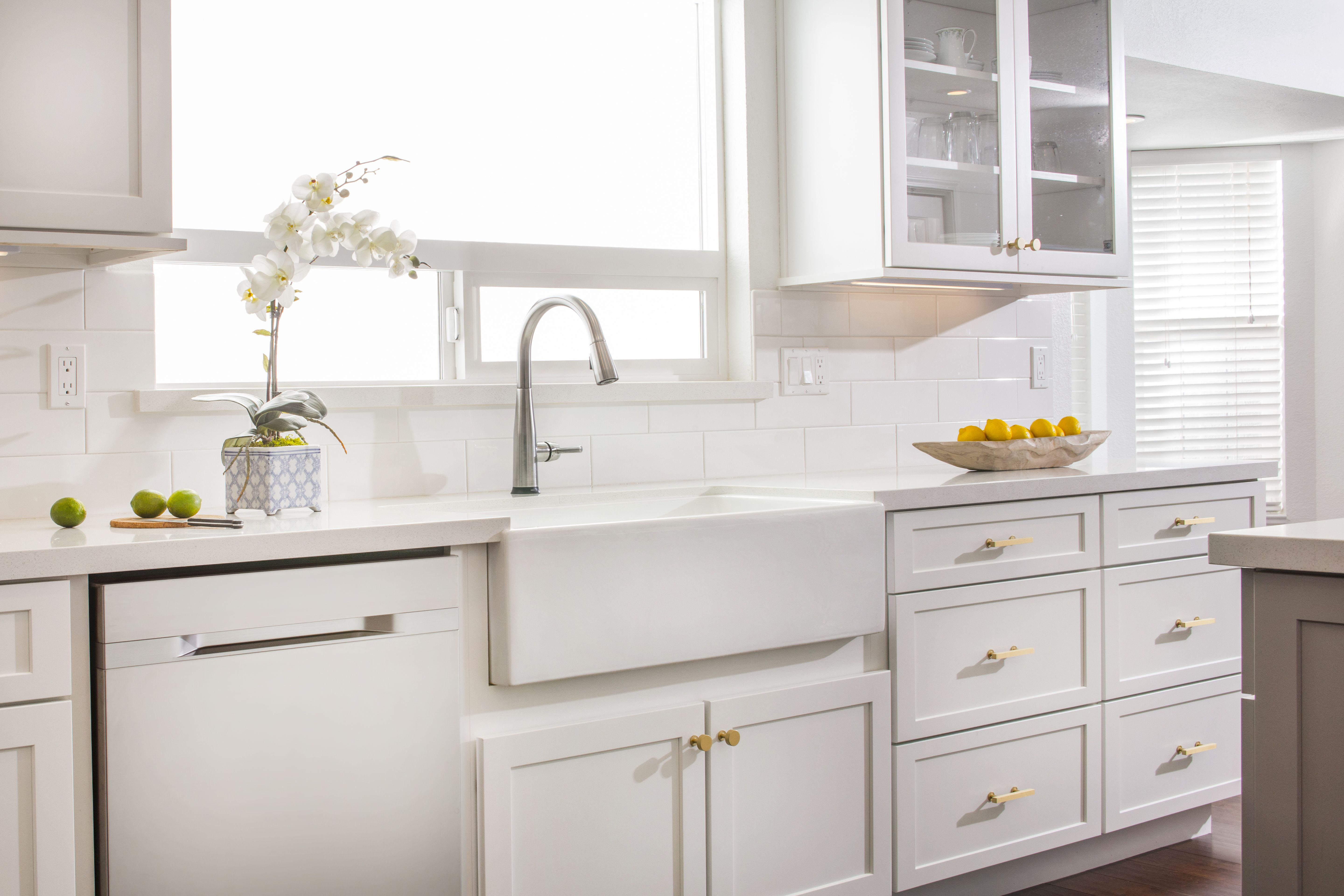 Bright, open residential kitchen featuring white shaker ...