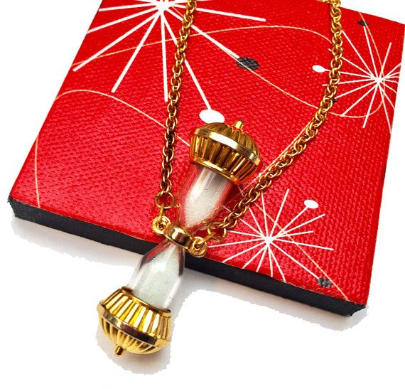 For your consideration is this sand hourglass pendant necklace - it consist of a gold tone metal hou
