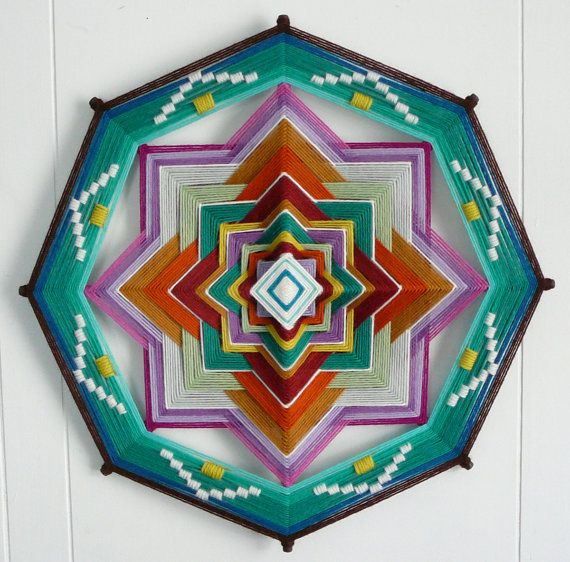 Fio colorido e madeira entrelaçando o dito fio sucessivamente até expressar o desenho de uma Mandala...