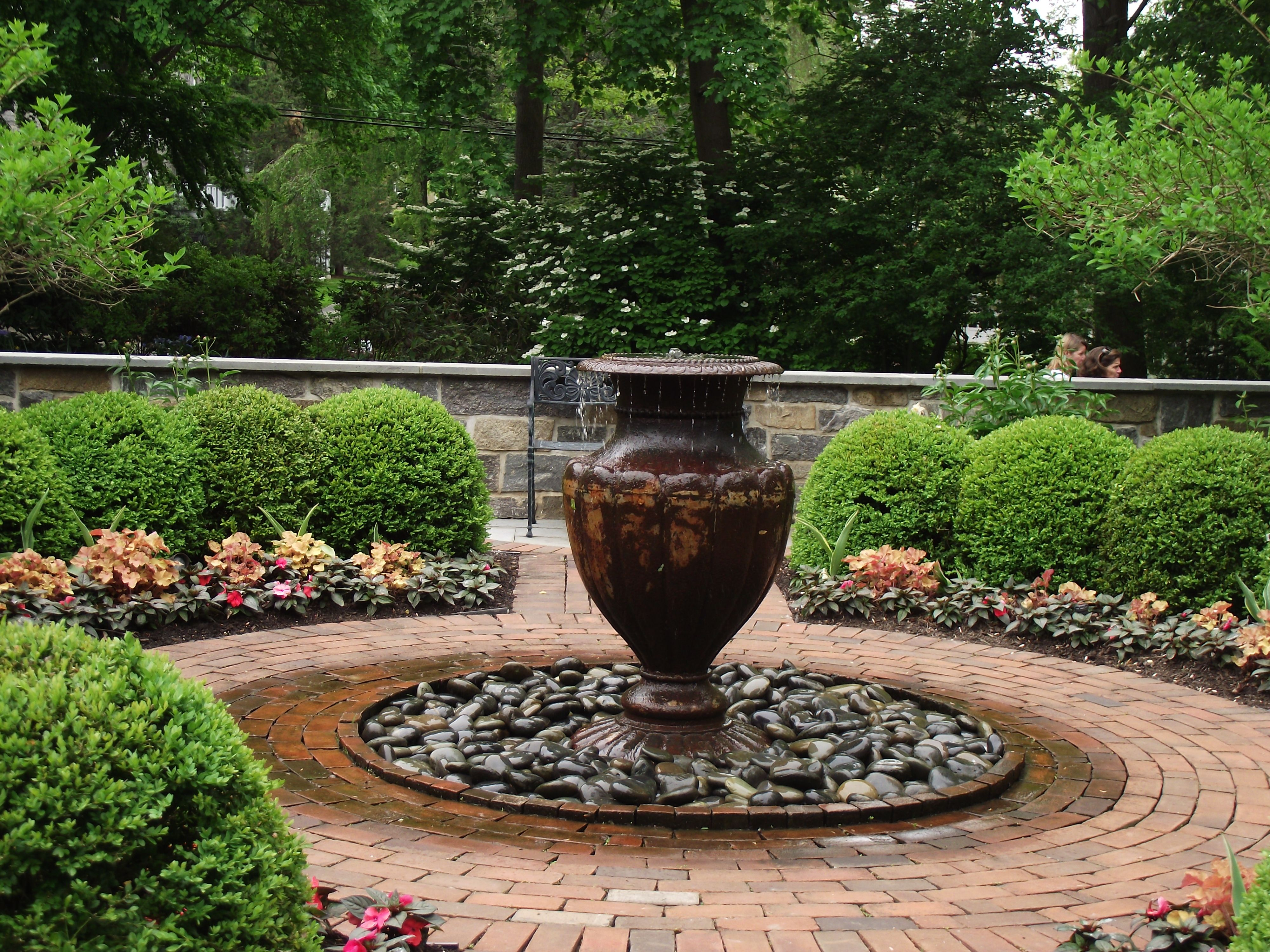 Iron Fountain Urn On River Rock Covered Below Grade Basin Surrounded By Brick Fountain Rock Cover Fountains
