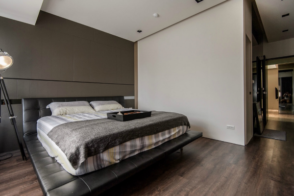 Stone and wood make a dark masculine interior the bedroom keeps its own masculine