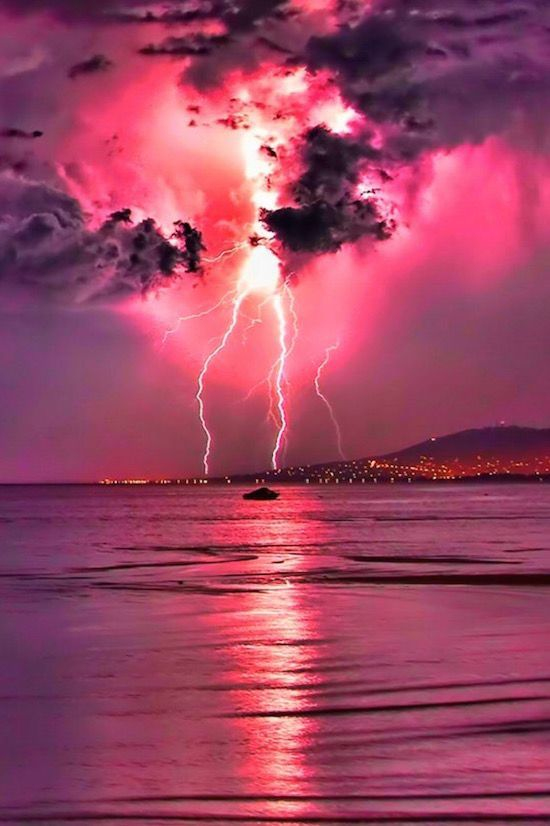 Beautiful lightning storm over the water in a pink sky.