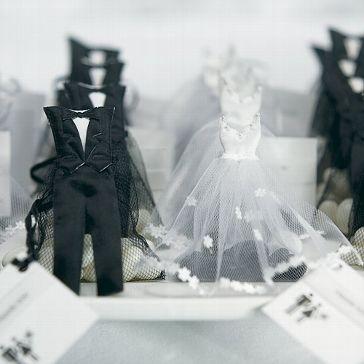 Kleine Mandelsäckchen im Anzug und Brautkleid für die Gastgeschenke auf der Hochzeit