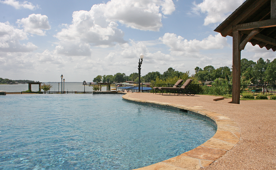 Resort-style Pool ~ The beautiful infinity edge pool has a 5 foot waterfall, giving swimmers the illusion swimmers of water rolling directly into Cedar Creek Lake.