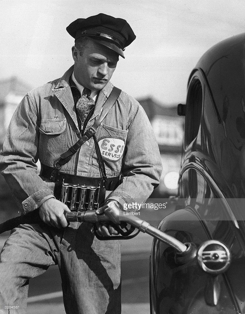 A gas station attendant, wearing an Esso uniform, fills a