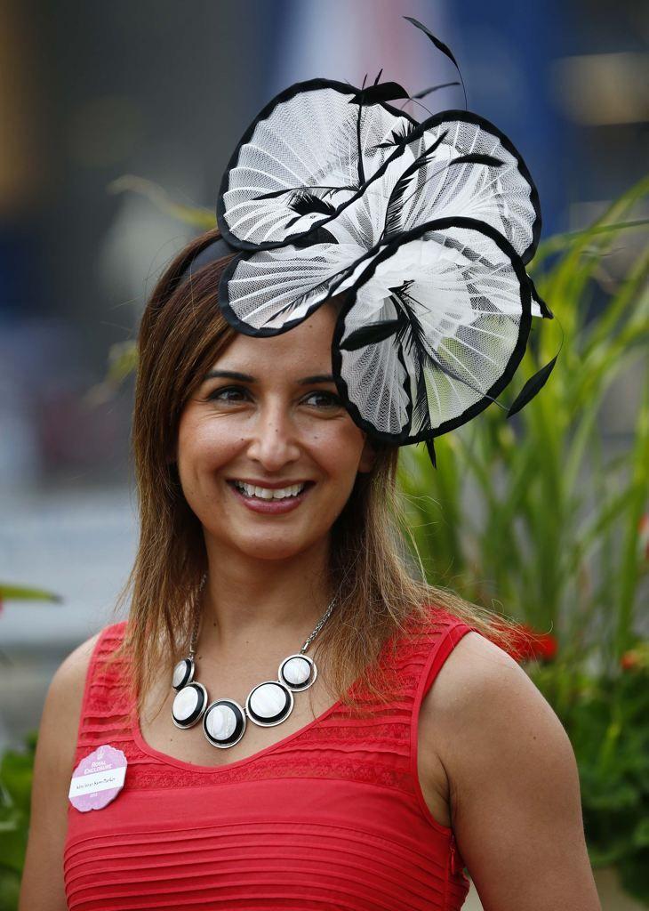 915e047e7ddf Racegoer Larisa Katz adjusts her hat as she arrives for Ladies  Day at the  Royal