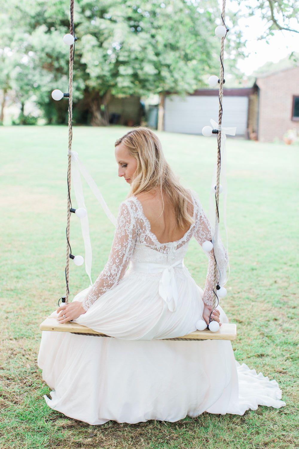 Bride sits on an outdoor garden swing with fairy lights -   Image by Camilla Arnhold - Naomi Neoh Fleur blush wedding dress for a beautiful peach and online dating themed back garden wedding with unique gift ideas for bridesmaids