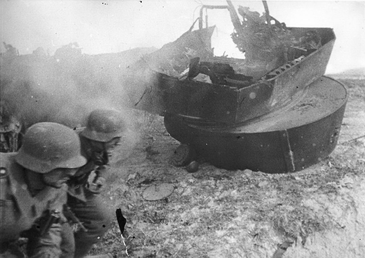 German soldiers during battle moving past a destroyed Soviet light tank T-26 destroyed near Leningrad. 1941.