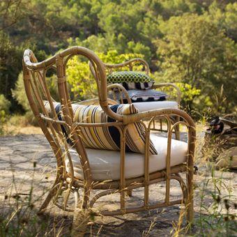 auf einer terrasse steht mastholmen sessel f r drau en aus rattan mit einem wei en sitzpolster. Black Bedroom Furniture Sets. Home Design Ideas