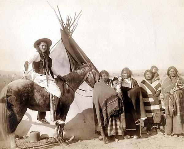 The image shows Four Lakota Sioux women standing, three holding infants in cradleboards, and a Lakota man on horseback, in front of a tipi, probably on or near Pine Ridge Reservation.  1891 by Grabill, John C. H., photographer.