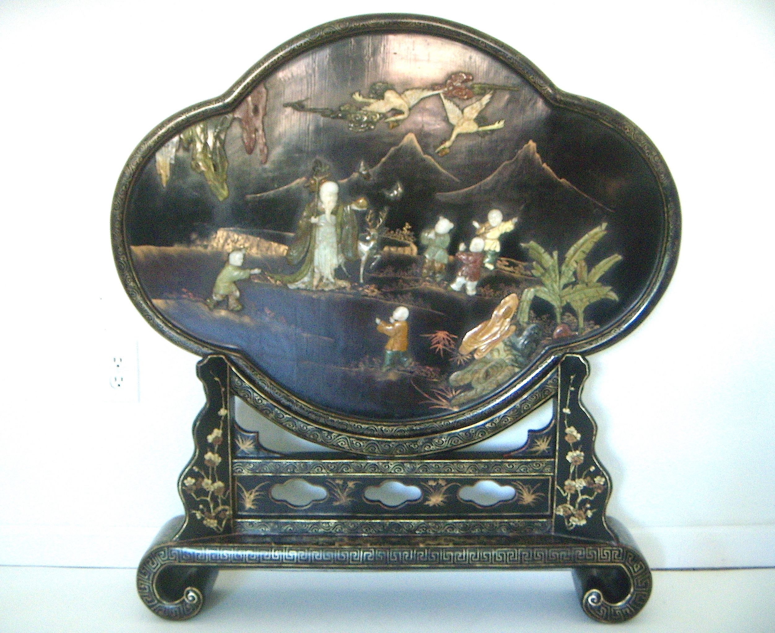 Magnificent and one of a kind black lacquer Chinese Fire Screen or Room Divider on matching scroll display stand made for the export market late 19th. C, early 20th. C. Quatrefoil shaped screen depicts five children at play surrounding 'Sau', (one of the three wise men representing longevity).  Find on Chairish soon.