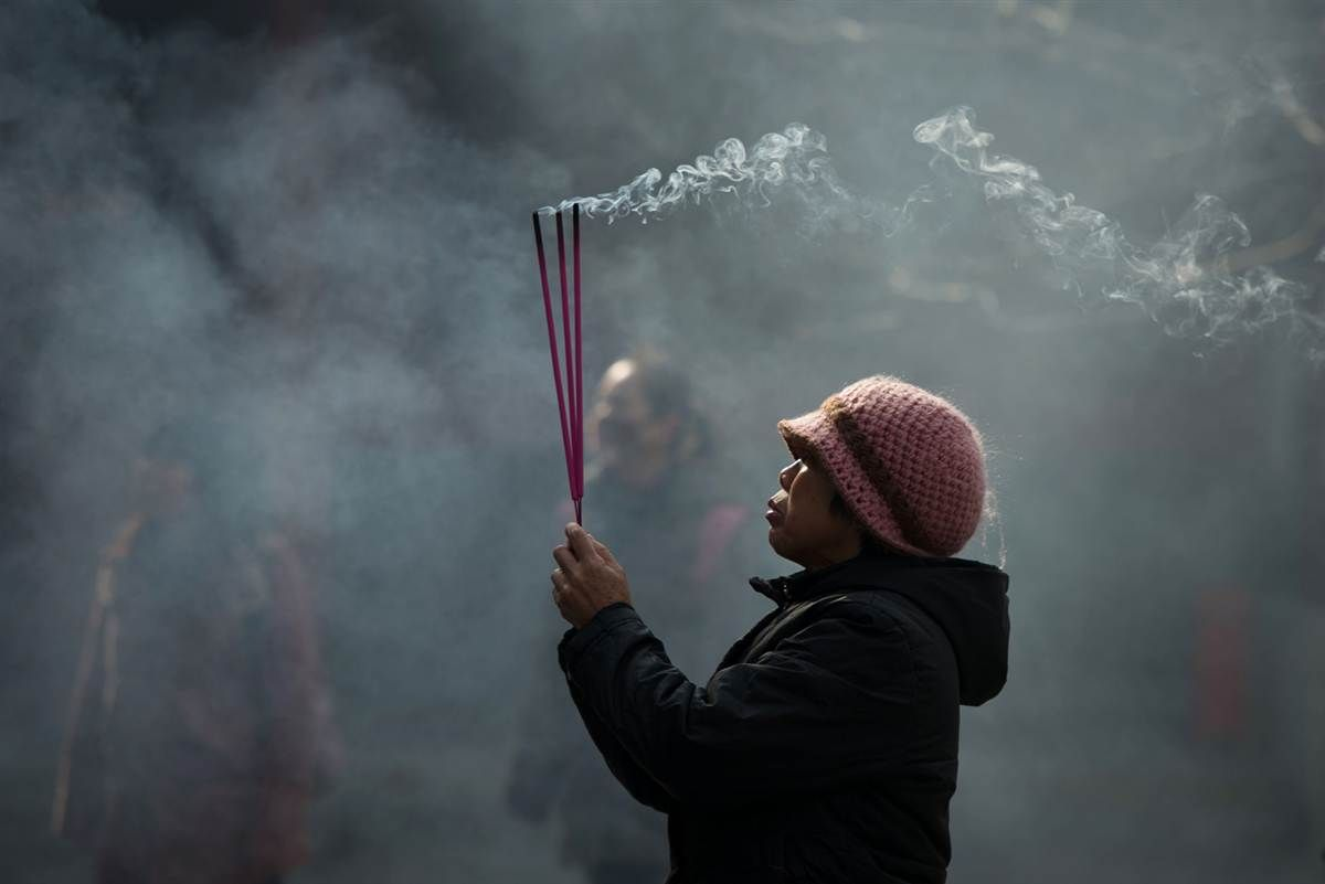 A worshipper burns incense while offering prayers at the Yonghegong lama temple in Beijing.  Ed Jones / AFP - Getty Images
