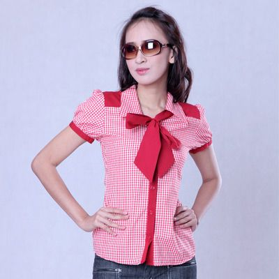 Red and white checkered blouse. Short sleeved. Front tie red bow. Front button placket. Matching Ruthie Hairband sold separately.