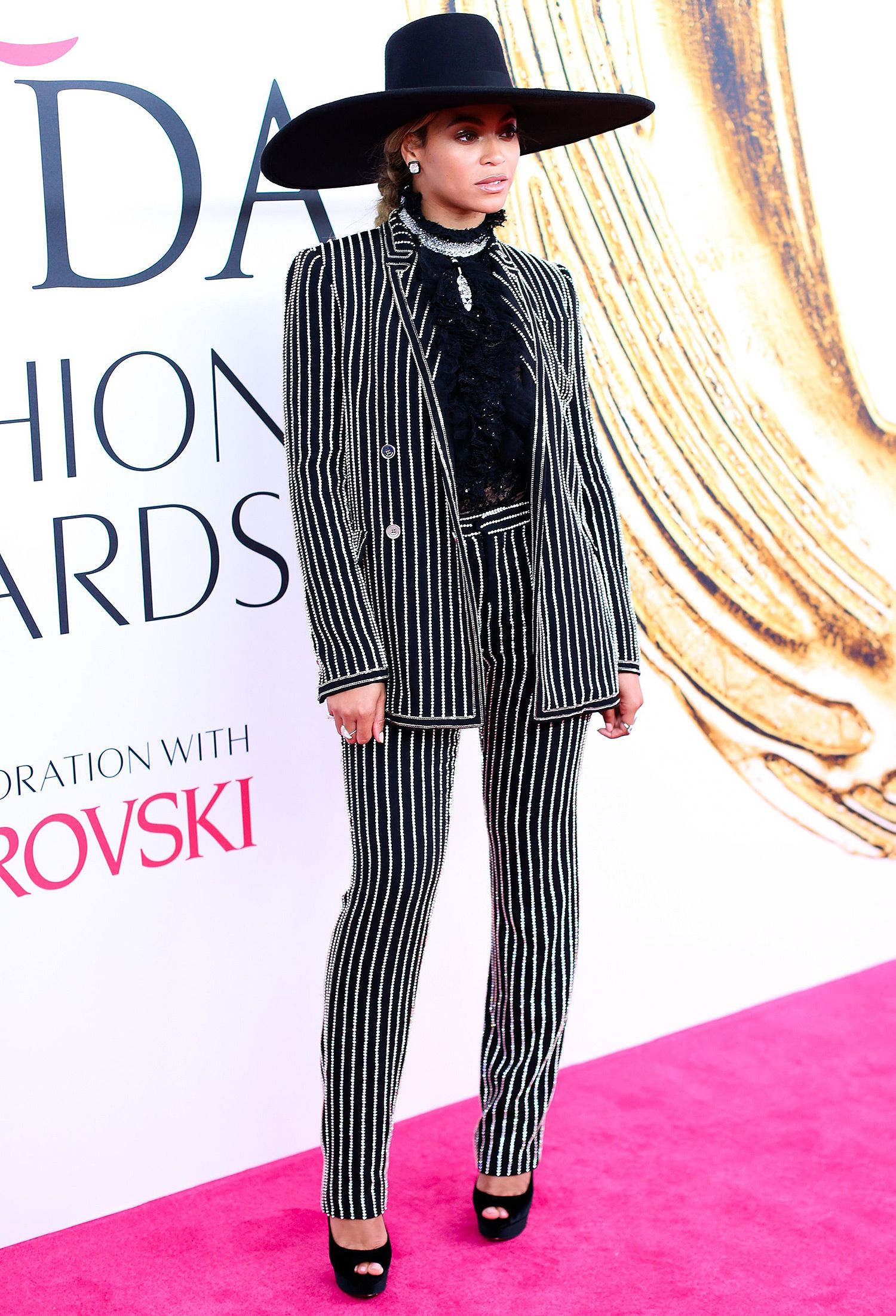 4d5927a21b02 CFDA Awards 2016  Beyonce is wearing a black white pinstripe Givenchy Haute  Couture pantsuit with a black hat and black Louboutin peep toe pumps.