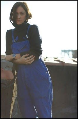 Blue dungarees, black polo-neck and tucked in hair |