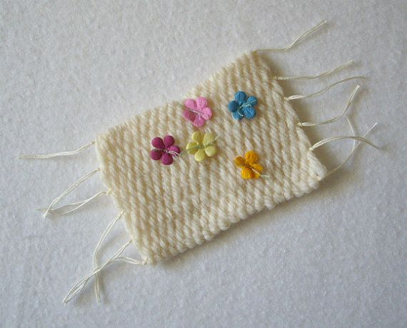 Small, rectangular weaving with a simple and sweet design. This handcrafted piece of art features tiny paper flowers, delicately attached with