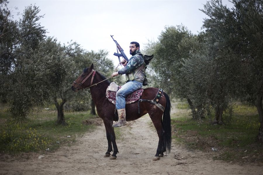 A Free Syrian Army member on his horse near the Turkish