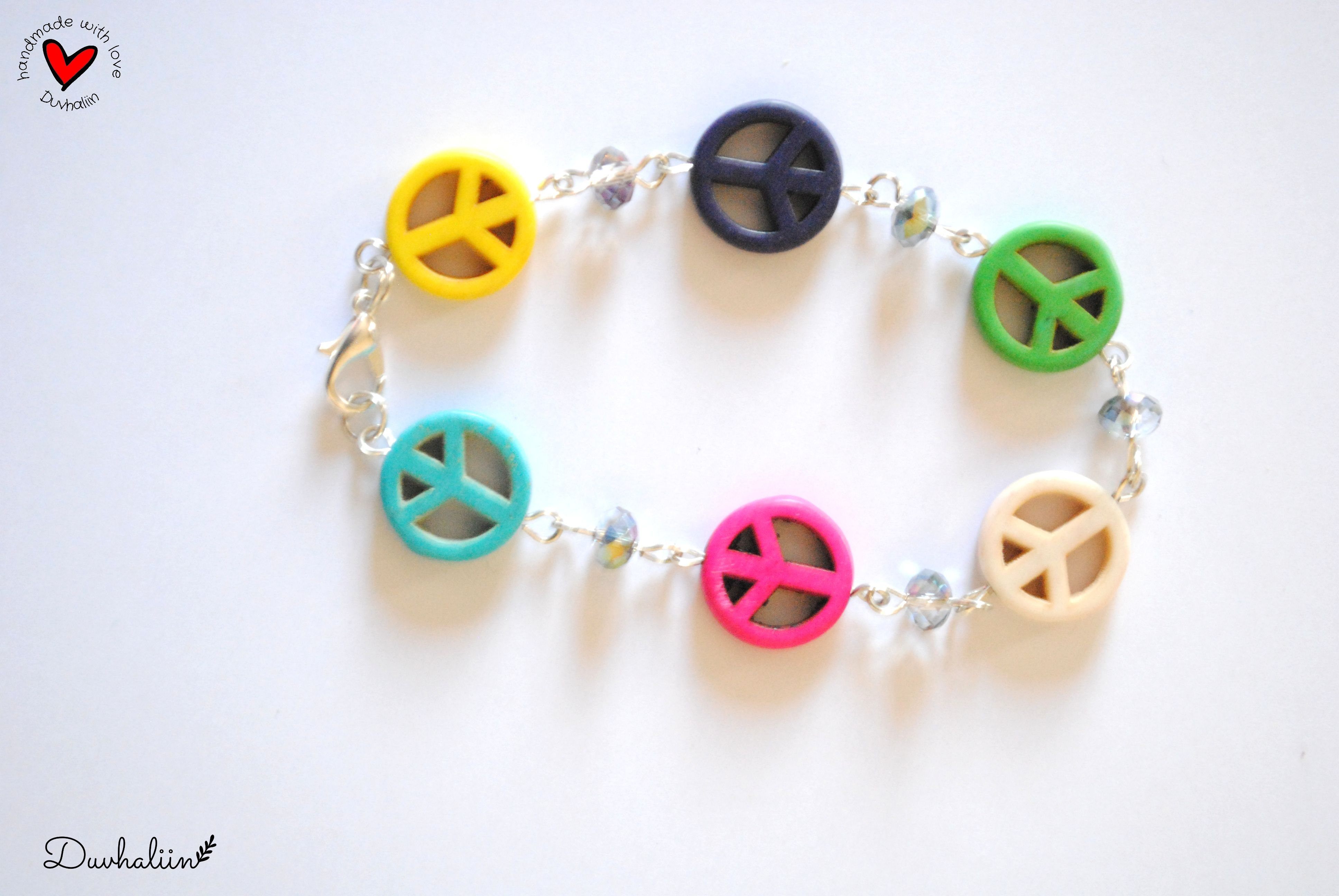 Pulsera ajustable con detalles en color plateado, cuentas de howlita con el simbolo de amor y paz y cuentas de cristal en color tornasol.