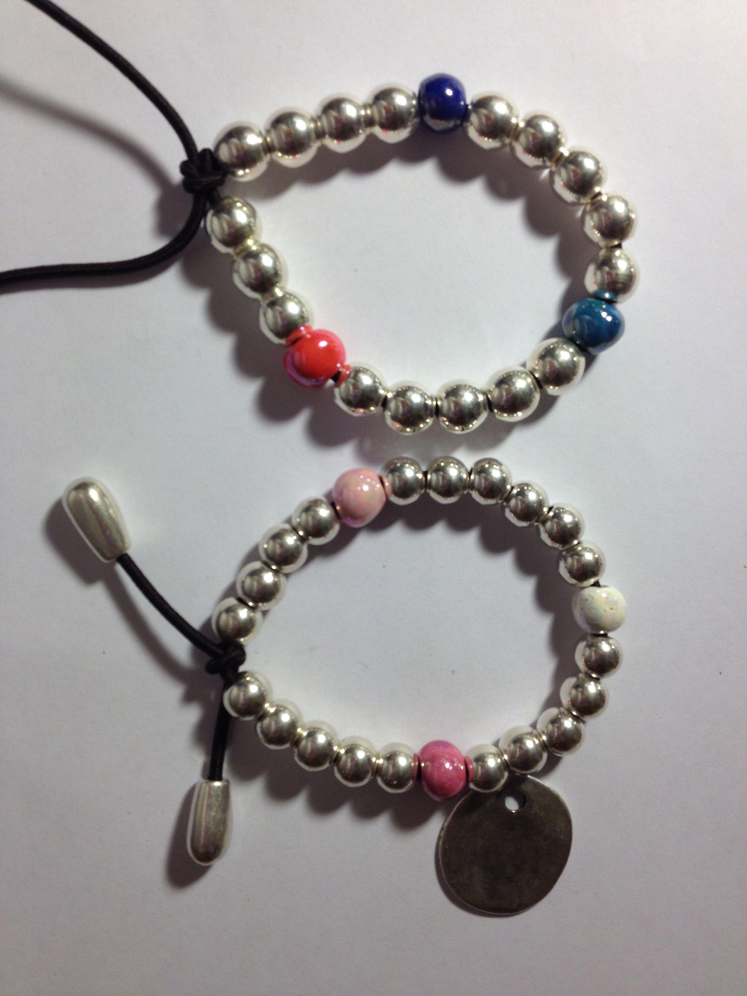 084b6ba8304c Pulsera elástica de bolas de zamak con baño de plata y 3 bolas de cerámica  de color. Lleva placa personalizada con el nombre