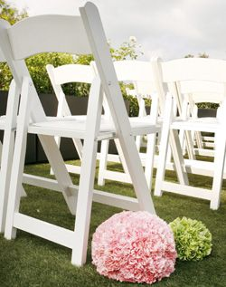 white resin chair with padded seat used for wedding ceremony we