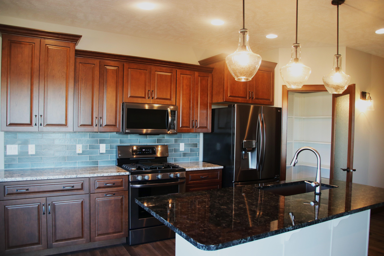 Kitchen with granite, tile backsplash, and Cherry cabinets ...