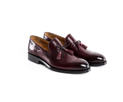 Calfskin tassel loafer with plain toe and brogue details.