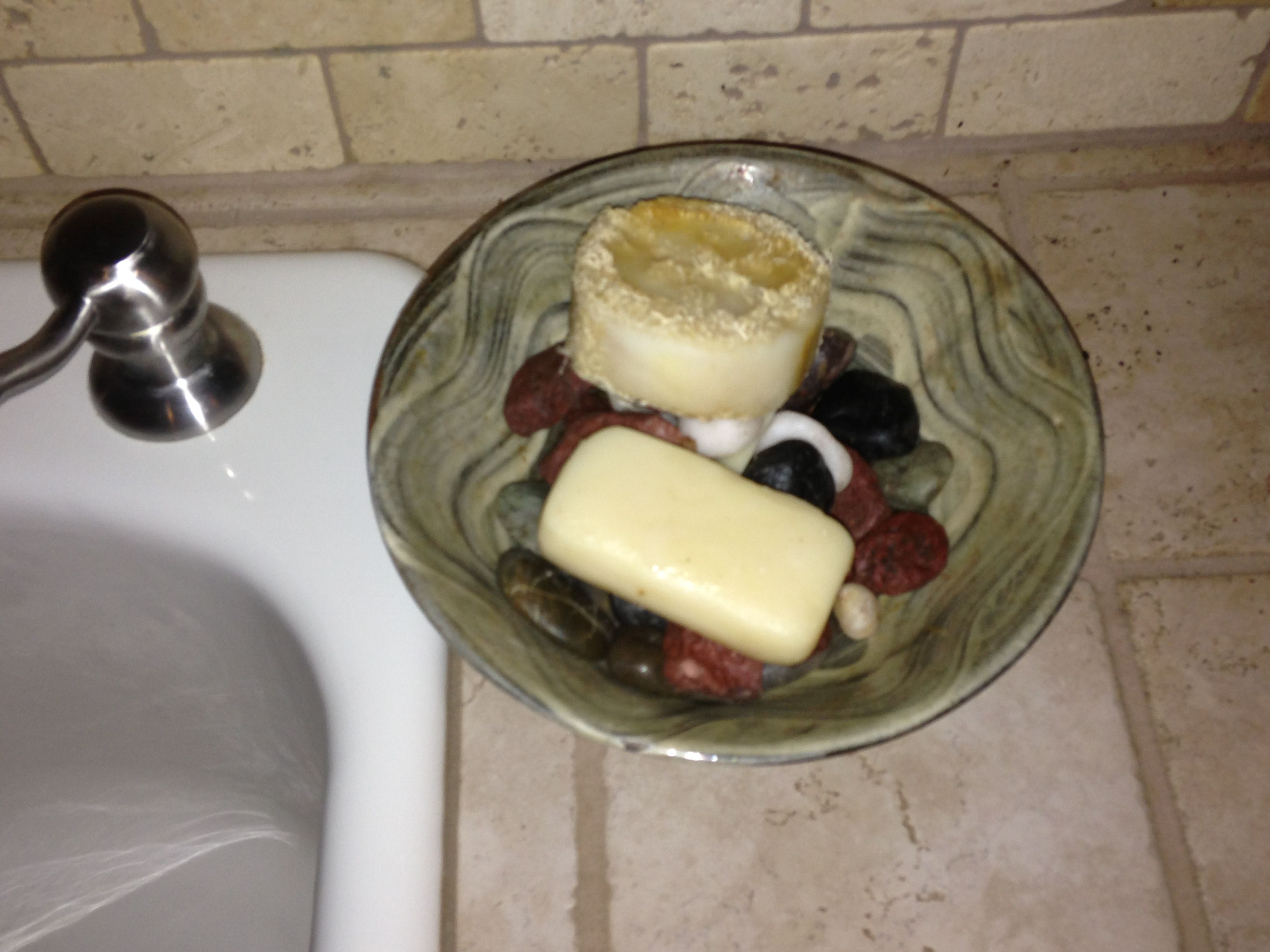 Ceramic bowl with small rocks in it. Set beside your kitchen sink to put your hand soap in to drain.