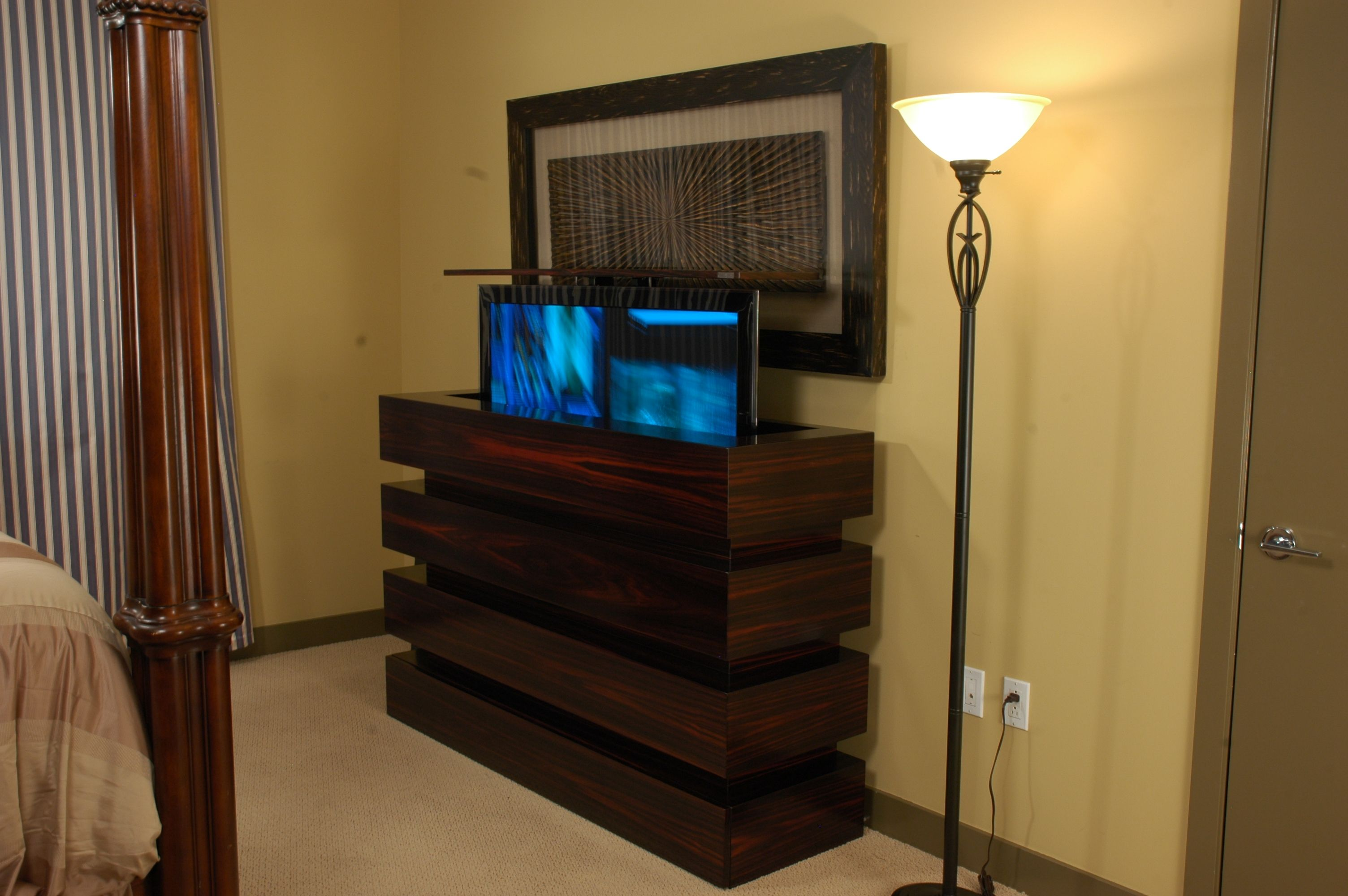 here is a tv lift cabinet showing tv half way up against a wall in front