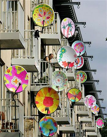 """Children dish up street art  A man looks out from a balcony amid satellite dishes that have been given an artistic makeover in Amsterdam.         The project """"pimp"""" the dishes was the initiative of a Dutch artist working with pupils in an area known as """"satellite city"""", inhabited predominantly by first and second-generation immigrants.     The hooks on the roof are used to move furniture in and out of upstairs flats, using a rope and pulley, in traditional buildings with narrow staircases."""