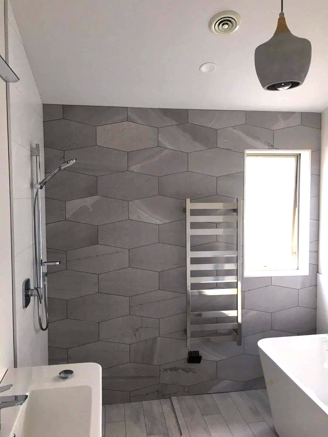 Luxury Bathrooms Tauranga stone cut grey hexagonal feature wall in a very stylish bathroom