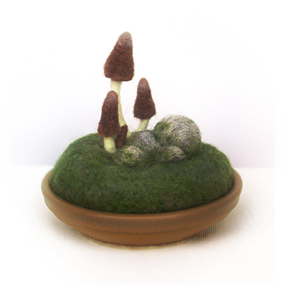 Brown pointy mushroom caps with cream-colored, gently flexible stems grow among moss-covered stones. This soft sculpture is needle felted from