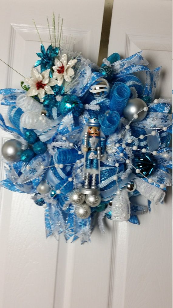 This deco mesh wreath features a Christmas nutcracker. It contains white and blue faux poinsettia flowers, ball ornaments, ribbons, floral picks, and lightbulb ornaments. It is primarily blue with silver and white accents.  W 18 H 17 Wreaths by Crazy Lady