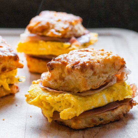 End your weekend right: garlic butter eggs and salty seared prosciutto on a make-ahead chive and cheddar biscuit.