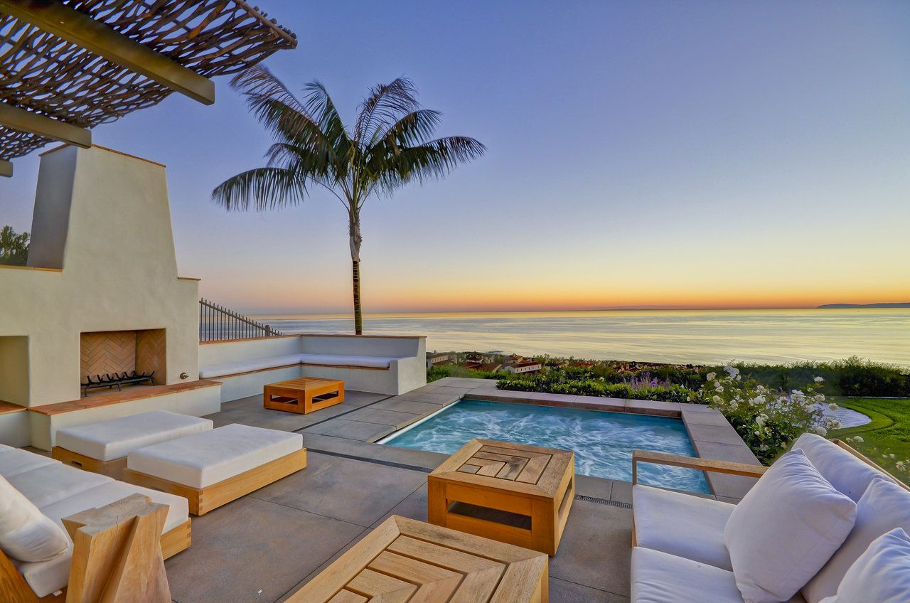 If the inground jet spa  jacuzzi with the beautiful ocean views wasn't enough, here this dream home captures the imagination and makes you want to call this mansion home. An added warm fireplace and high end custom teak patio furniture and white pillows and white cushions are just the icing on the cake.