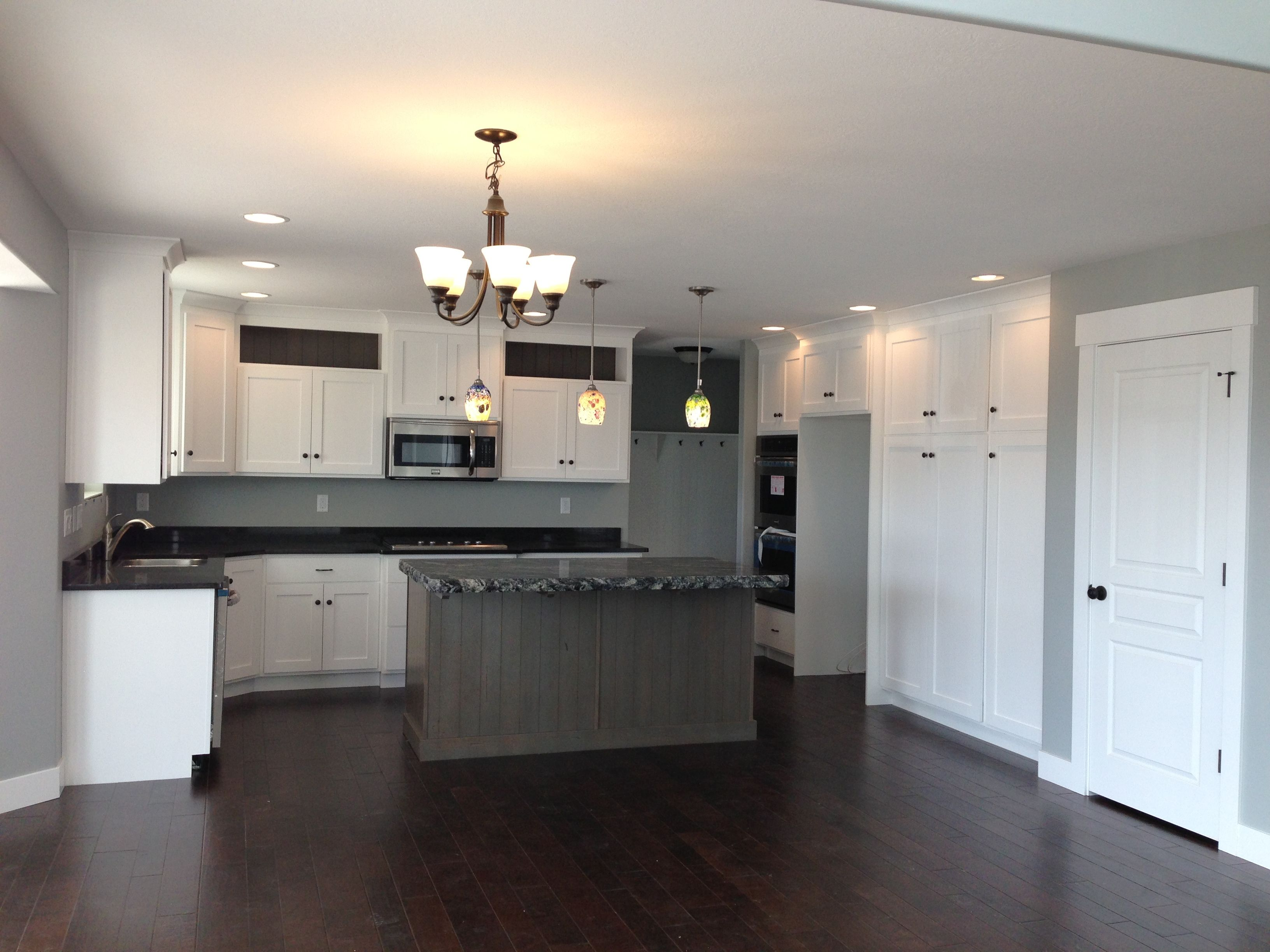 I Love The Dark Wood Floors With White Cabinets Not A Fan Of The Grey Island Though I Would Have L Elegant Kitchen Design Flat Interior Design White Cabinets
