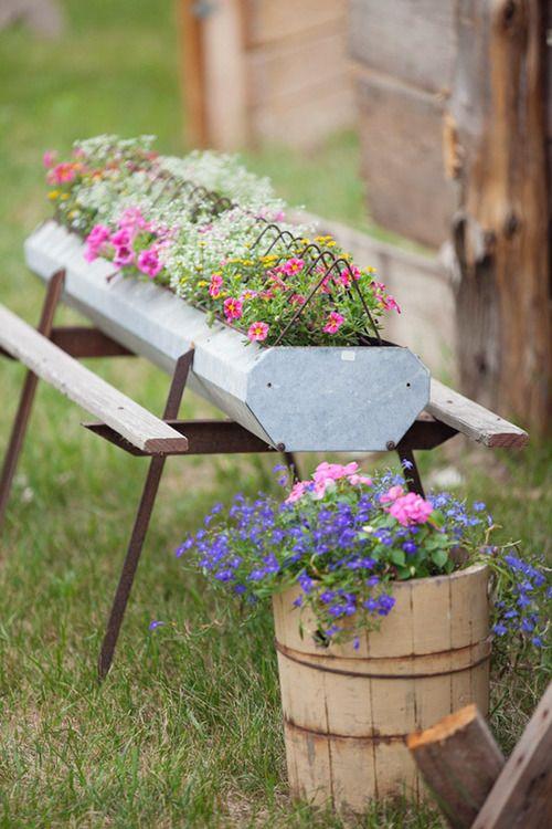 Old Garden Grub...chicken feeder & old wooden bucket stuffed with flowers.