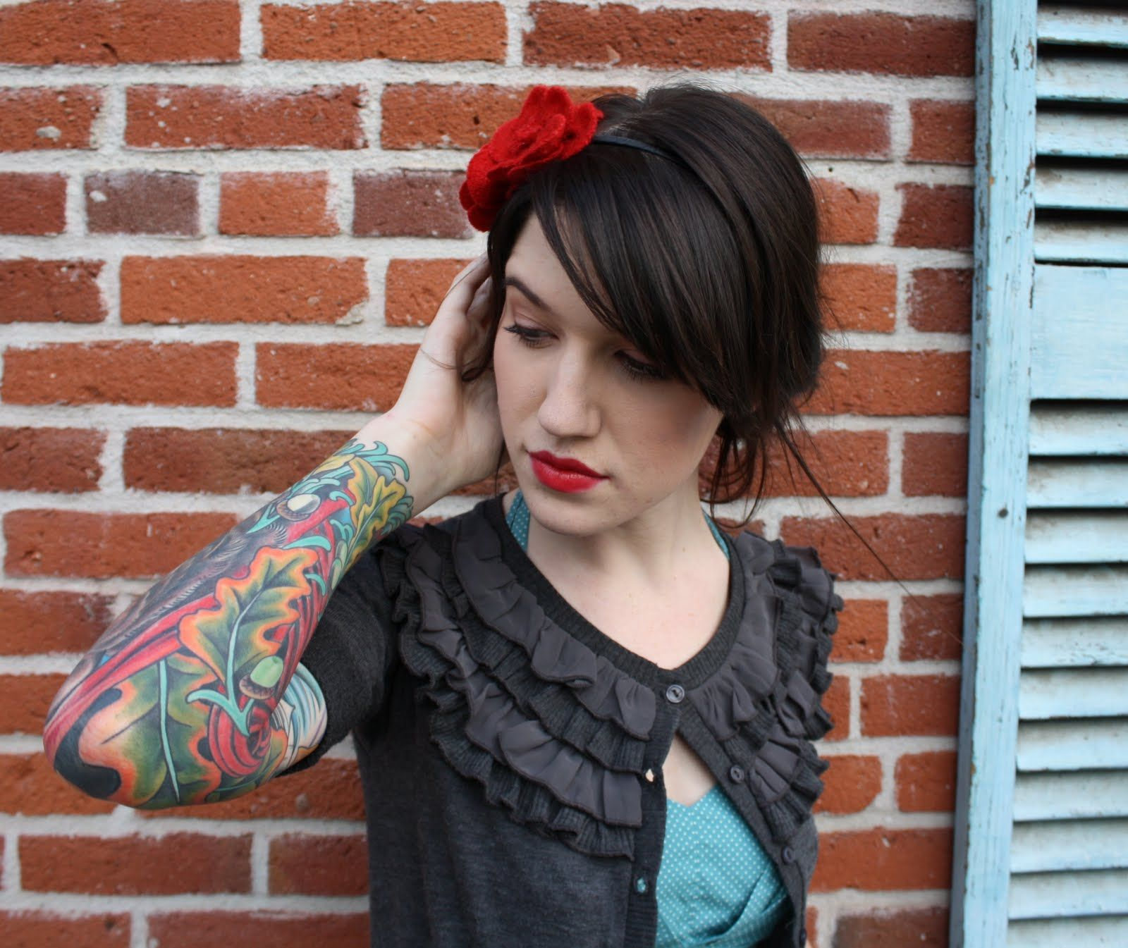 I like the look. Sweet cardigan with the aqua shirt, red lips and headband with her dark hair.