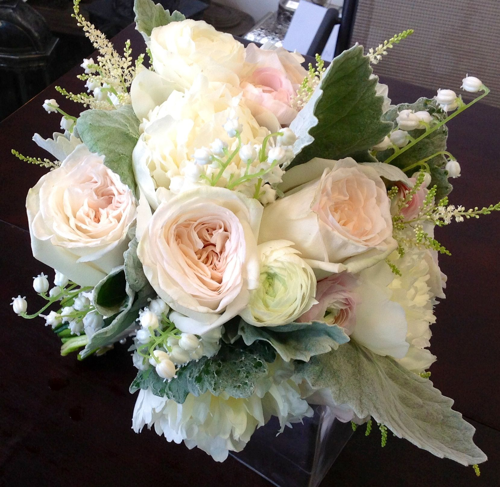 elegant wedding bouquet comprised of white peonies white ranunculus white lily of the valley light pastel pink english garden roses dusty miller