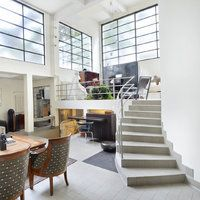 La pièce à vivre est éclairée par la lumière naturelle diffusée par de larges baies vitrées qui donnent sur une terrasse.
