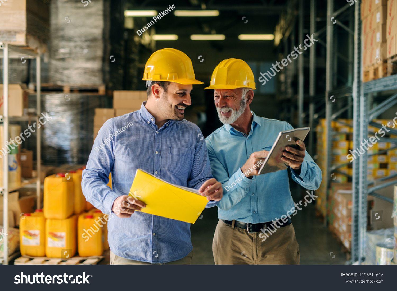Two Successful Smiling Business Man Walking Through Big Warehouse