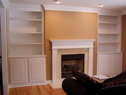 Custom Built Bookcases With Crown And Dentil Moulding On Each Side Of A Gas Fireplace