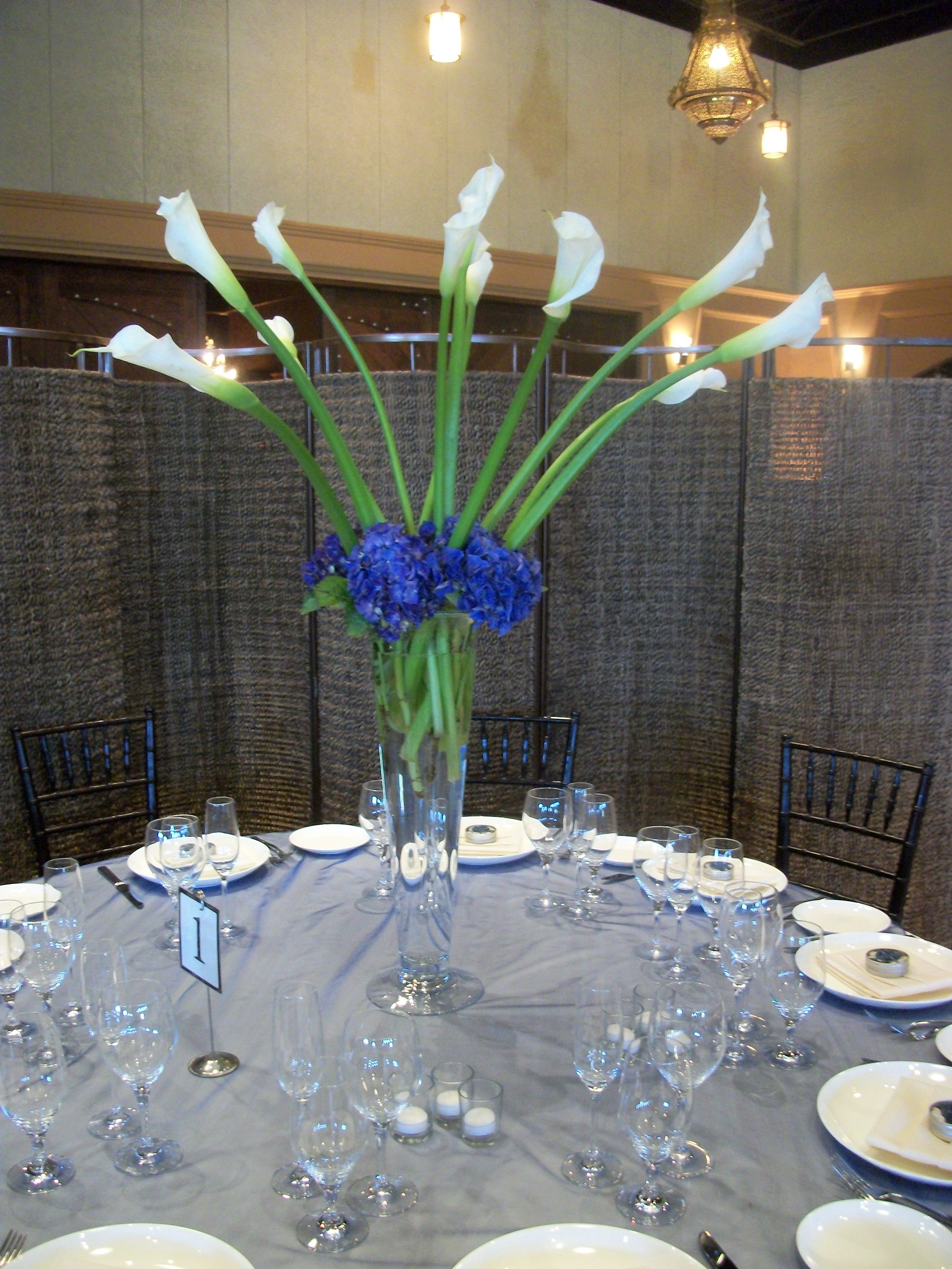 Dark blue hydrangea tall white calla lilies in trumpet